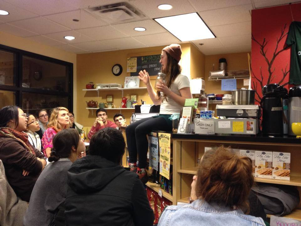 woman sitting on counter in front of group of people teaching kombucha brewing class