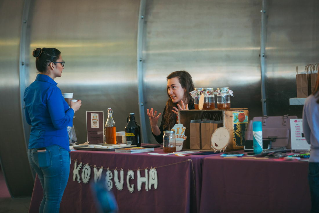 woman sitting at kombucha brewing table talking to another woman
