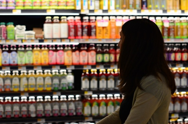 woman shopping for kombucha in grocery store in front of wall of kombucha bottles