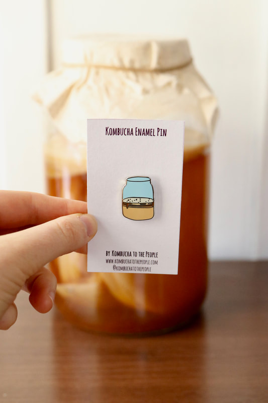 kombucha enamel pin of kombucha scoby in a jar in front of real jar of kombucha with SCOBY