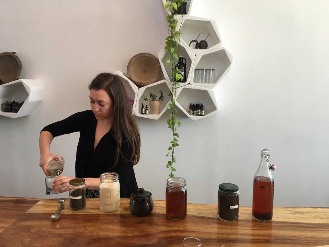 woman sitting on counter in front of group of people teaching kombucha brewing class and pouring kombucha
