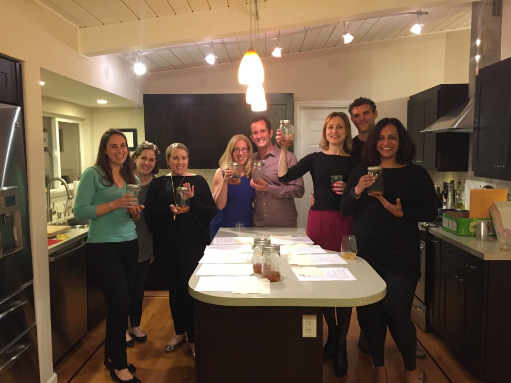 private kombucha class with people standing in kitchen smiling holding kombucha scobys